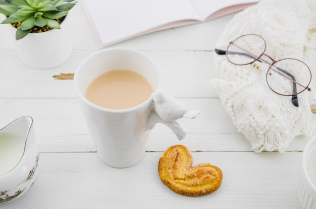 Palmiers or elephant ear puff pastry cookie with porcelain white tea cup on wooden desk Free Photo