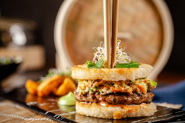 Pan-asian cuisine concept. japanese sushi burger made from rice bread, chicken and pork meat patties, lettuce and wasabi sauce. serving dishes with french fries. copy space Premium Photo