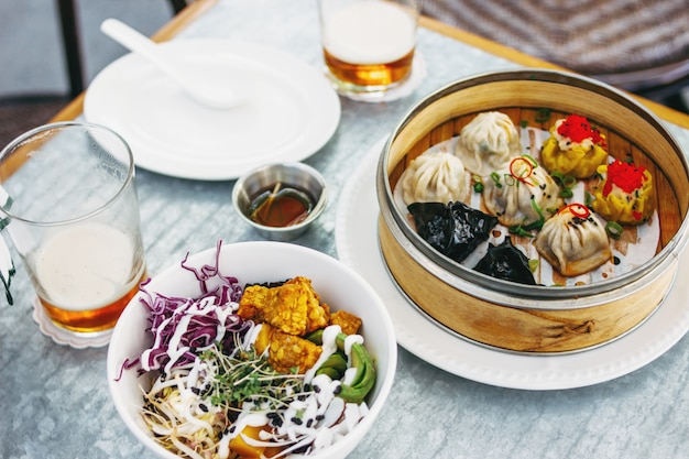 Pan-asian food - different dim sums in bamboo bowl and salad. lunch for two with beer Premium Photo