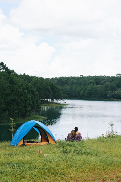 A pan shot of couple cuddling at the river near the tent with their backs to the camera Free Photo