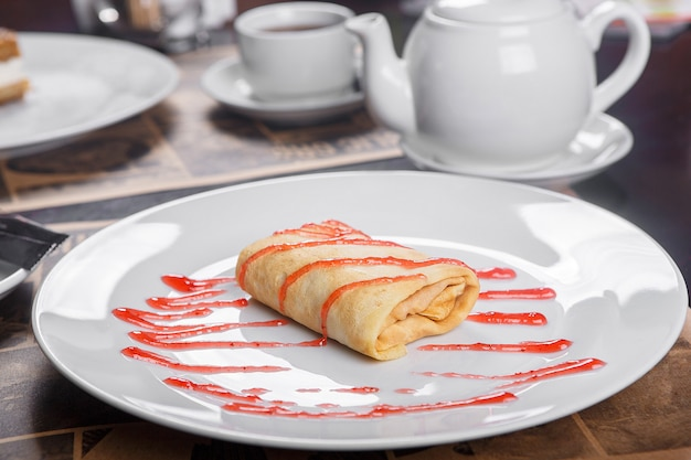 Pancake stuffed on a plate with jam Premium Photo