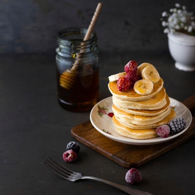 Pancake tower with banana raspberries and honey Free Photo