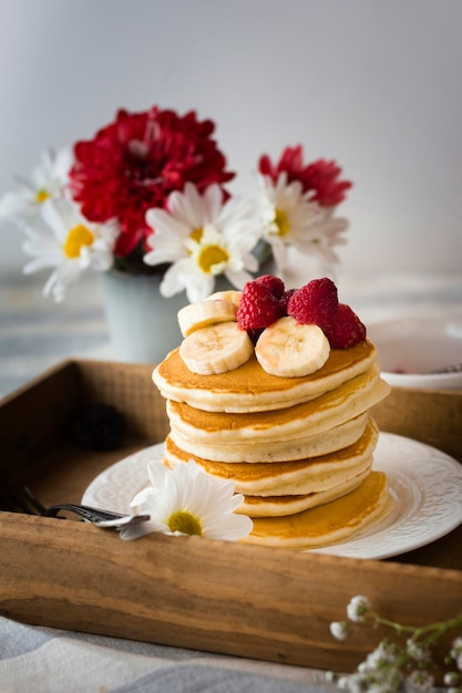Pancake tower with banana and raspberries Free Photo