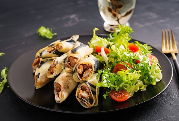 Settimana del pancake. shrovetide. frittelle arrotolate ripiene di carne di pollo e verdure. crepes salate. Foto Gratuite