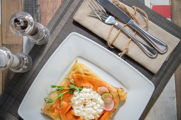 Pancake with salmon and sourcream and dille on a white plate Premium Photo