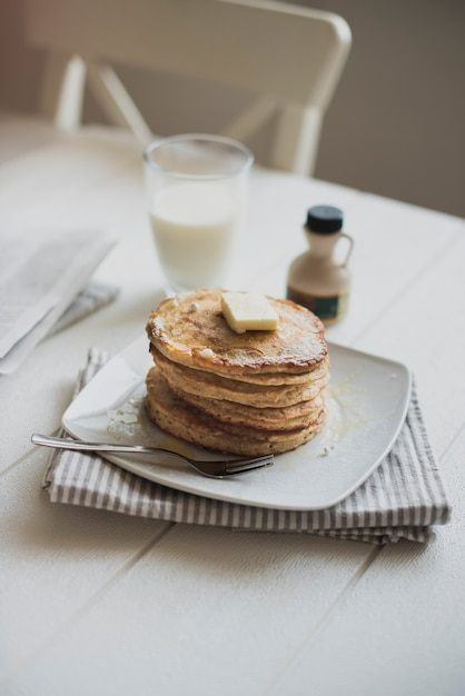 Pancakes and milk for breakfast on table Free Photo