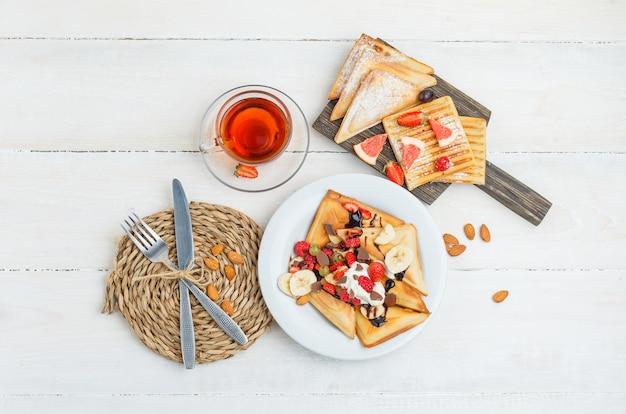 お茶、アーモンド、ナイフ、フォーク、ブドウ、ラズベリーと木の板のパンケーキ 無料写真