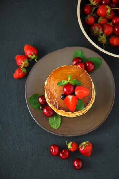 Pancakes in a plate with strawberries, mint, honey and cherry on a dark black background. Premium Photo