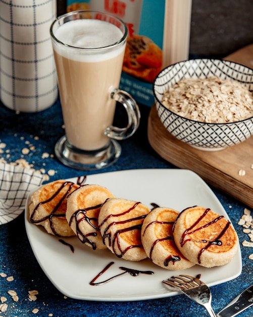 Pancakes topped with chocolate syrup and cappuccino Free Photo