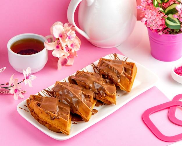 テーブルの上のチョコレートと紅茶とパンケーキワッフルパンケーキ 無料写真