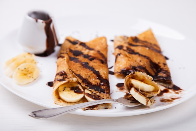Pancakes with banana and chocolate topping Premium Photo