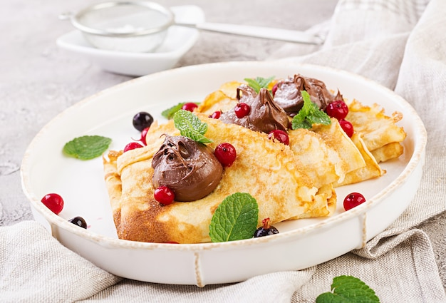 Pancakes with berries and chocolate decorated with mint leaf. tasty breakfast. Free Photo