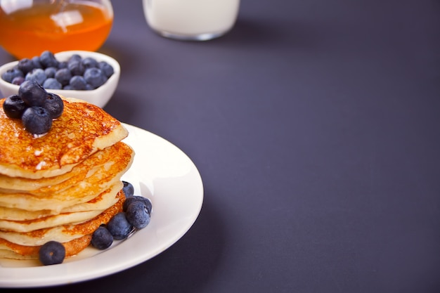 Pancakes with berries and honey on the black background Premium Photo