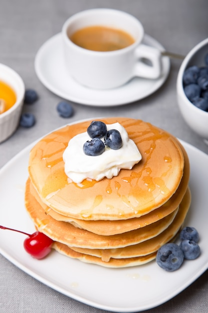 Premium Photo Pancakes With Blueberries Cherries Sour Cream Honey And Coffee Close Up Selective Focus