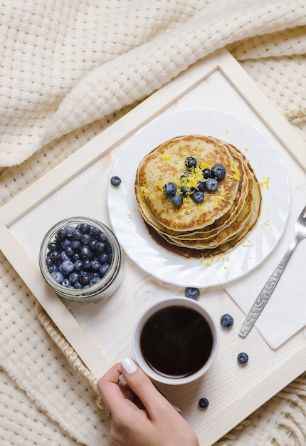 Pancakes with blueberry and cup of coffee on a wooden tray. Premium Photo