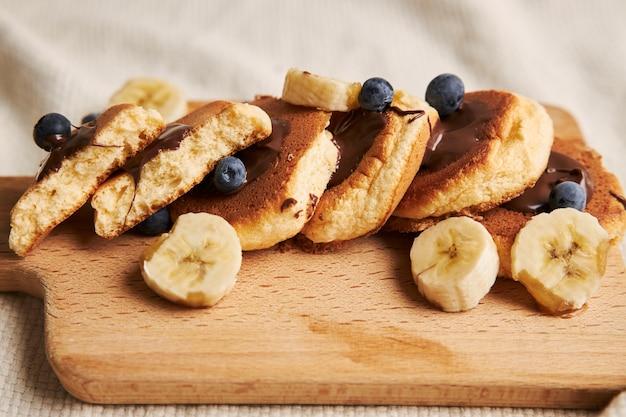 白の後ろの木のプレートにチョコレートソース、ベリー、バナナのパンケーキ 無料写真