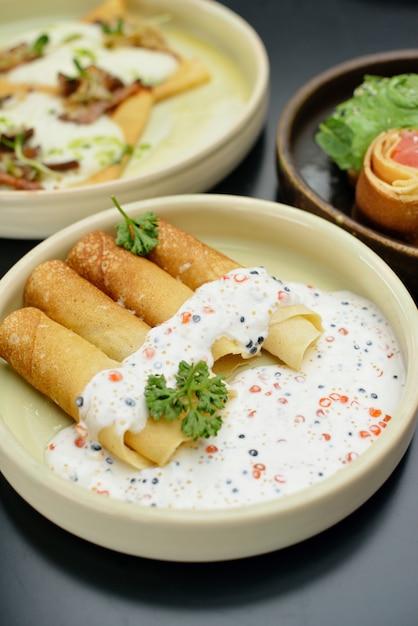 Pancakes with fish salmon, caviar and cream sauce. restaurant menu Premium Photo