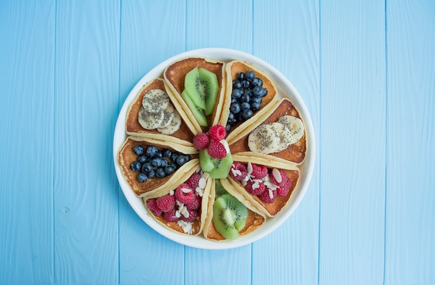 Pancakes with fresh berry on a blue wooden . pancakes with fruits. summer homemade breakfast. Premium Photo