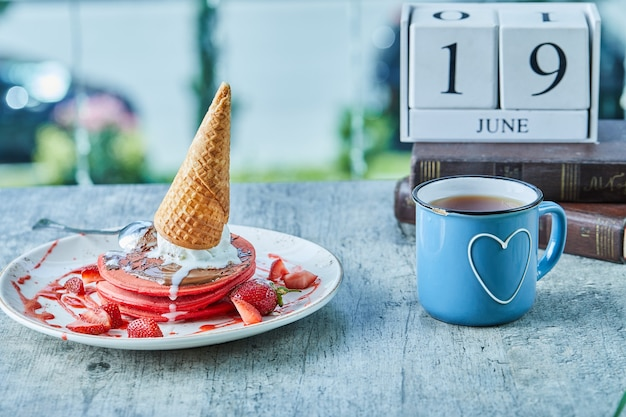 Pancakes with ice-cream cone, strawberry and hot tea on the calendar and books surface Free Photo