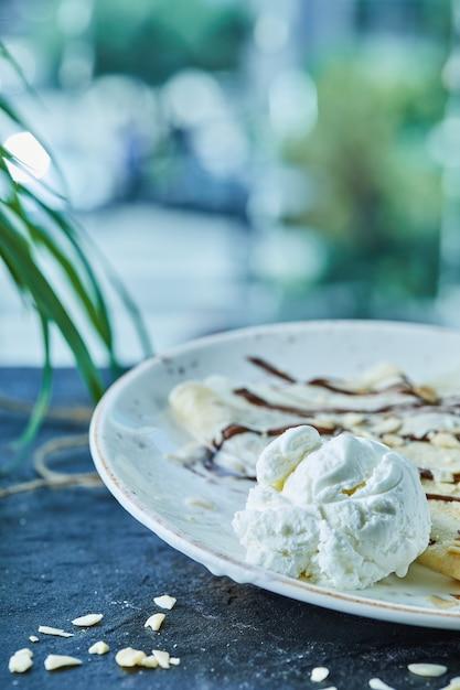 어두운 표면의 흰색 접시에 아이스크림, 뿌리, 초콜릿 팬케이크 무료 사진