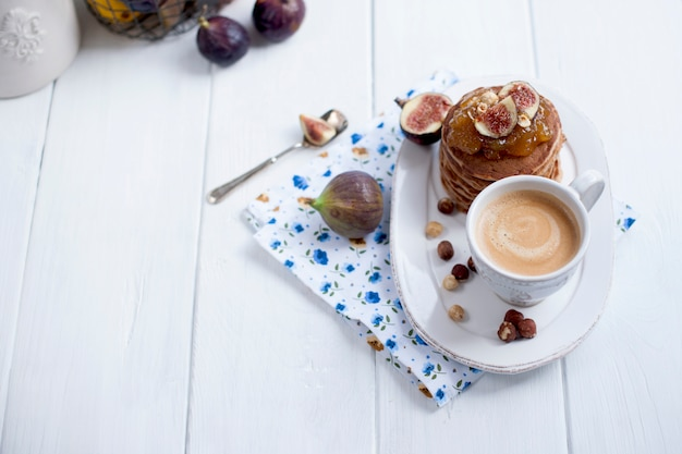 Pancakes with jam and figs on a white plate and a cup of coffee on a white background Premium Photo