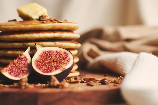 シロップ、バター、イチジク、木の板にローストナッツのパンケーキ 無料写真