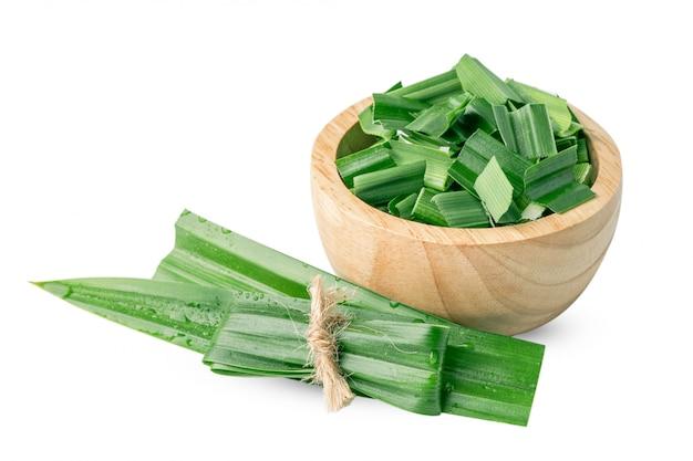 パンダンの葉と木製のボウルにスライスして、アジア料理の味と香りを白で隔離。 Premium写真