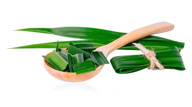 パンダンリーフとクリッピングパスとアジア料理の味と香りに白で隔離される木のスプーンでスライス。 Premium写真