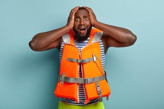 Paniking uomo afroamericano in giubbotto di salvataggio, afraids dell'attività sciistica estiva Foto Gratuite