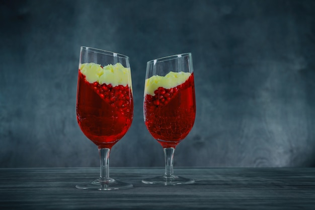 Panna cotta dessert with pomegranate seeds jelly on rustic wooden background. Premium Photo