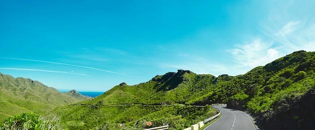 파노라마와 아스팔트 도로와 산과 푸른 하늘의 아름다운 전망은 푸른 피요르드와 이끼 산 사이 꼬불 꼬불 꼬불하다. 무료 사진