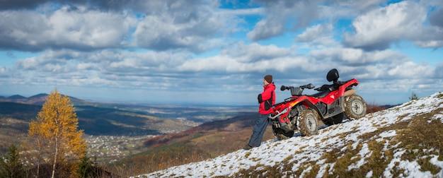 Panorama. man standing near atv quad bike on snowy mountain top Premium Photo