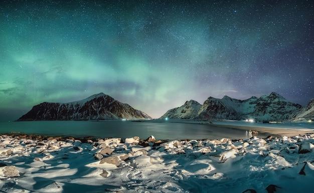Skagsanden 해변, Lofoten 섬에서 눈 덮인 해안선이있는 산맥 위에 별이있는 오로라 보 리 얼리 스의 파노라마 프리미엄 사진