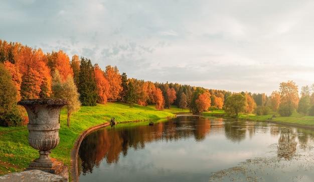 호수에 의해 빈티지 돌 꽃병과 붉은 나무와 가을 공원의 파노라마 프리미엄 사진