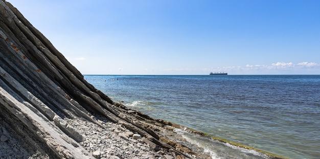 바다의 파노라마입니다. 절벽의 기슭에 아름다운 돌 야생 해변, 구름과 밝은 푸른 하늘과 수평선에 배. Gelendzhik 리조트 주변. 러시아, 흑해 프리미엄 사진