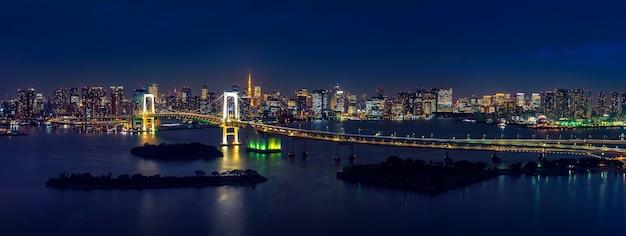 Панорама городского пейзажа токио и радужного моста в ночное время. Бесплатные Фотографии