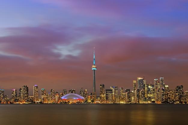 Панорамный освещенный городской пейзаж центра торонто над озером онтарио в сумерках, торонто, канада Premium Фотографии