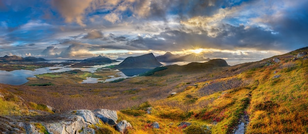 Panoramic shot of grassy hills and mountains near water under a blue cloudy sky in norway Free Photo