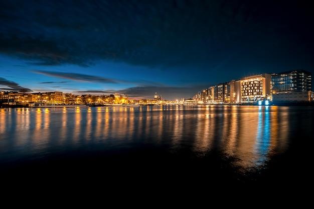 Foto panoramica di uno skyline notturno con riflessi di luce sull'acqua Foto Gratuite