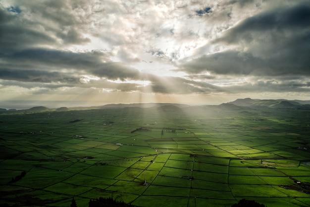 구름을 통해 빛나는 태양 광선으로 농업 분야의 파노라마 샷 무료 사진