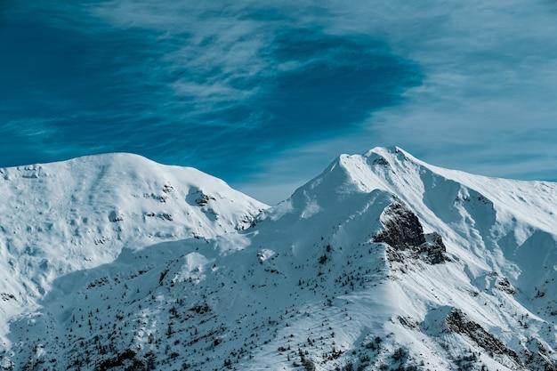 Панорамный снимок заснеженных горных вершин под пасмурным голубым небом Бесплатные Фотографии