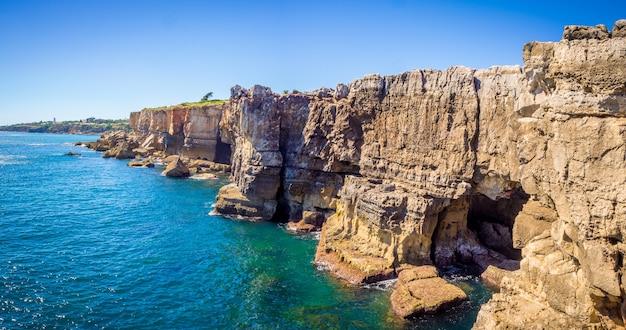 Панорамный снимок скал на берегу океана в кашкайше, португалия Бесплатные Фотографии