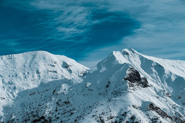 Panoramic shot of snow covered mountain peaks under cloudy blue skies Free Photo