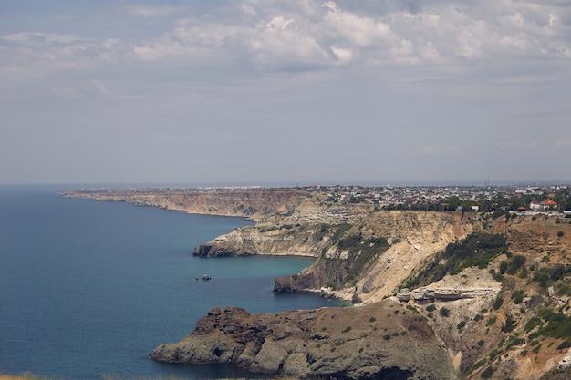 Vista panoramica della costa scoscesa con piccole città dal pacifico mare blu. seascape e lungo aspro litorale in una giornata estiva nuvolosa. natura, mare, vacanze, vacanze e concetto di destinazione turistica Foto Gratuite