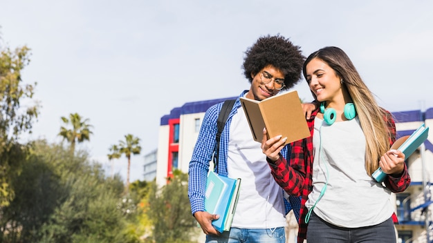 Panoramic view of diverse teenage couple reading the book outside the campus Free Photo