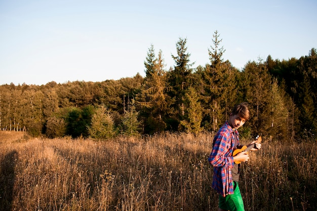 Panoramic view of forest and man playing ukulele Free Photo