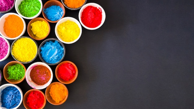 Panoramic view of holi color powder in the bowls on black background Free Photo