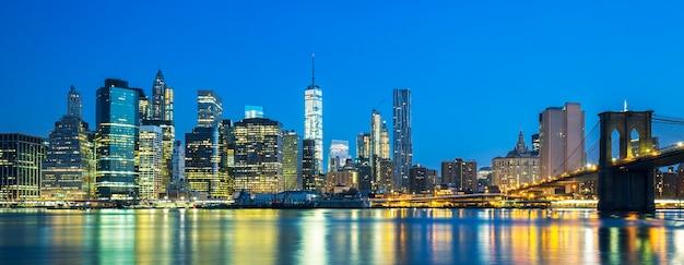 Vista panoramica di new york city midtown manhattan al tramonto con grattacieli illuminati su east river Foto Gratuite