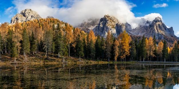 ドロミテ岩山とカラフルな木々の秋のアントルノ湖のパノラマビュー Premium写真