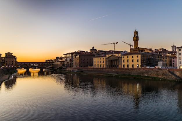 Панорамный вид на знаменитый понте веккьо с рекой арно на закате во флоренции, италия Бесплатные Фотографии